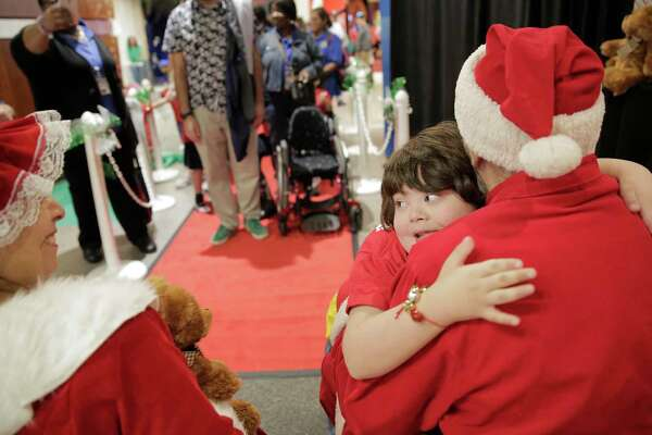 "A student from Houston Heights Elementary gives Santa a hug during the John P. McGovern Museum of Health and Medical Science's ""Touch, Smell and Hear"" event on Monday. More than 400 children with physical and mental disabilities participated."