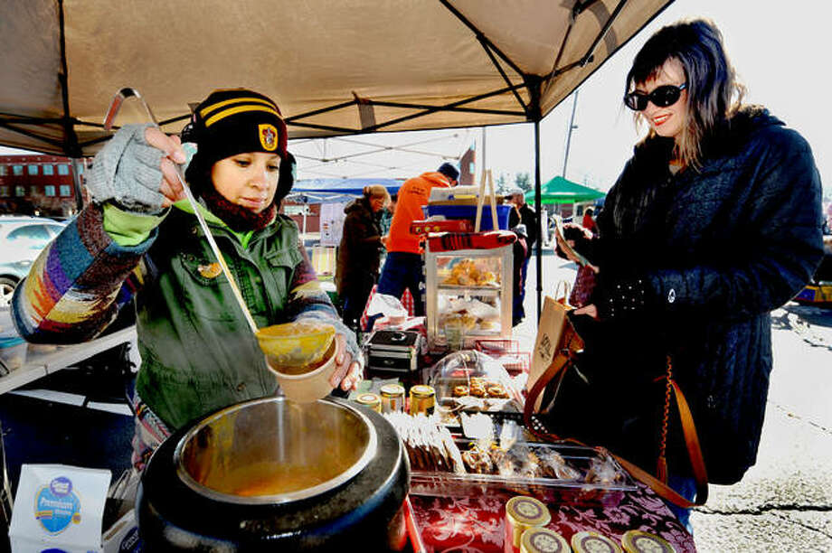 Queens Cuisine Tea Room employee Lupe Gomez, left, pours some pumpkin soup into a cup for Holly Hampton during this year's Winter Market on Saturday in downtown Edwardsville. Photo: Thomas Turney|For The Intelligencer
