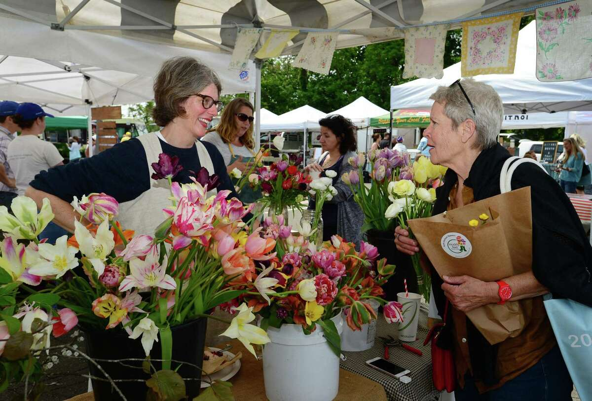 Kristin Burrello of the Muddy Feet Flower Farm Coop in Ashford chats with customer and Westport resident Barbara Powell during the opening day of The Westport Farmers Thursday May 23, 2019, at 50 Imperial Ave. in Westport, Conn. The market runs through November 7 Thursdays from 10:00 AM to 2:00 PM.