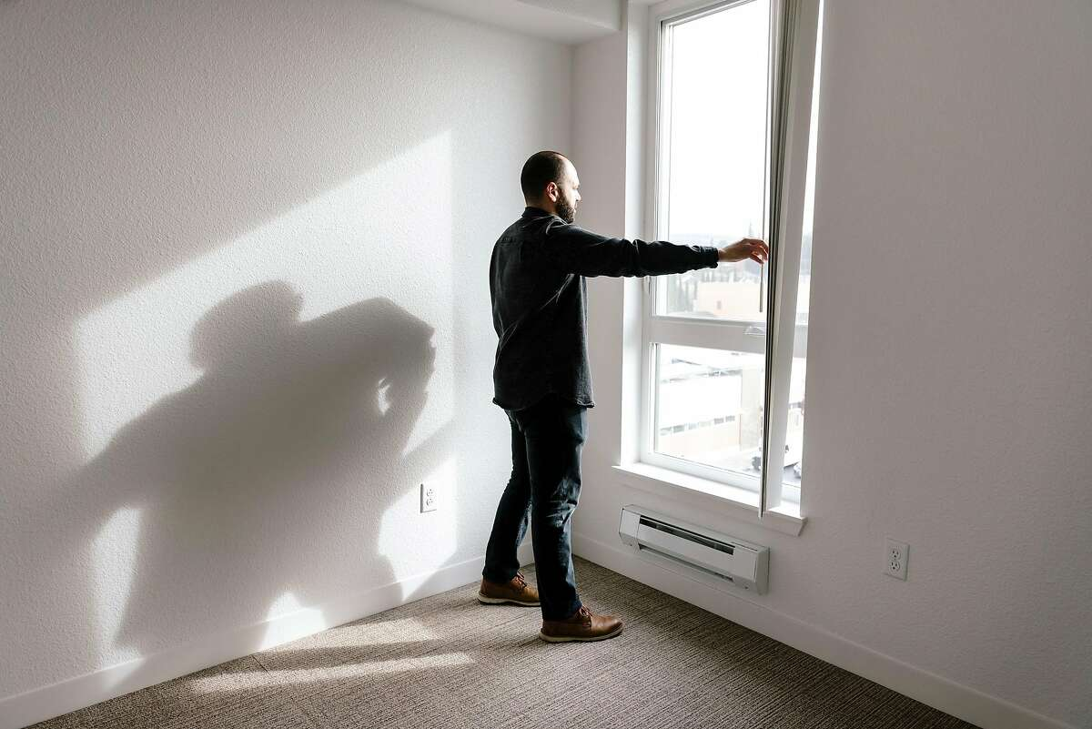 """Adam Kuperman, senior project manager for Satellite Affordable Housing Associates, opens the blinds in an apartment in the company's new 37 unit affordable housing development on International Boulevard called """"Camino 23"""", in Oakland, California, Thursday, December 5th, 2019."""