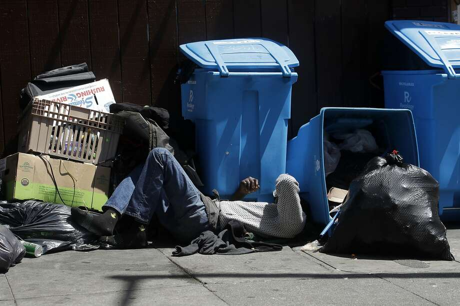In this Aug. 21, 2019, file photo, a homeless man sleeps in front of recycling bins and garbage on a street corner in San Francisco. Photo: Jeff Chiu / Associated Press