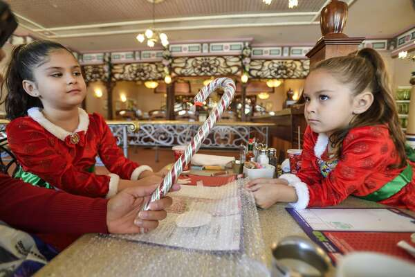 Abby McCruden,, left, and her sister, Allie McCruden, take giant candy canes seriously as they wait for a piece of a freshly-made candy cane at Disneyland in Anaheim, California, on Friday, December 1, 2017. The candy canes are so popular that visitors to the park need to get wristband with a return time to but the candy.