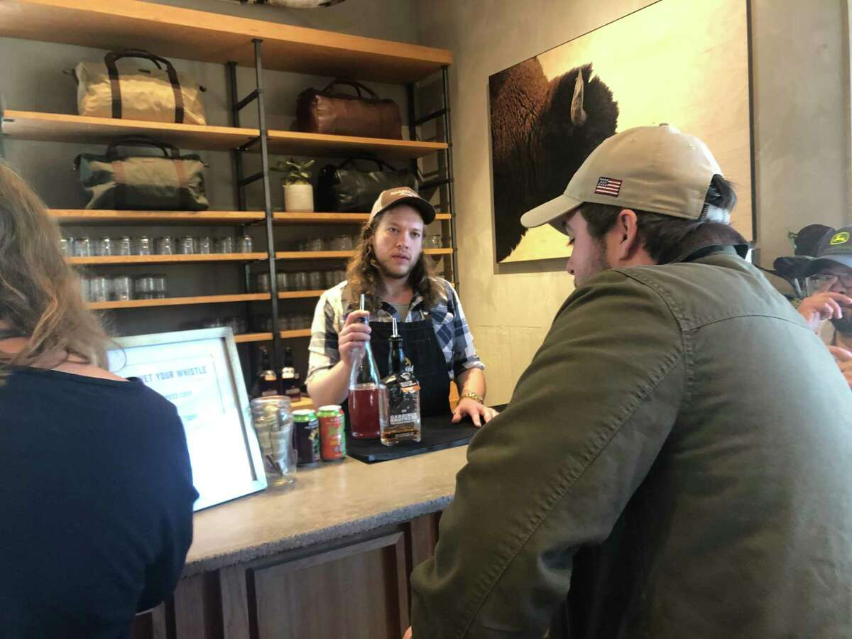 Rustyn Brandt works for Sourced Craft Cocktails, which serves the bars on weekends at the five Tecovas locations that opened this year. Here, he chats with a customer about the cocktail options.
