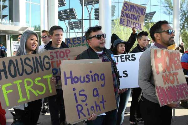 Protesters shout as they hold signs outside Las Vegas City Hall during a protest against the city council's ban on homeless camping on Wednesday, Nov. 6, 2019. Officials passed a law Wednesday making it illegal for the homeless to sleep on streets when beds are available at established shelters. (Bizuayehu Tesfaye /Las Vegas Review-Journal via AP)
