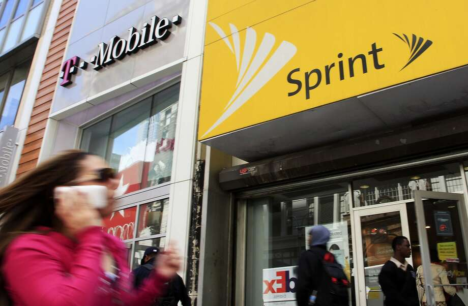 FILE - In this April 27, 2010 file photo, a woman using a cell phone walks past T-Mobile and Sprint stores in New York. Photo: Mark Lennihan, Associated Press