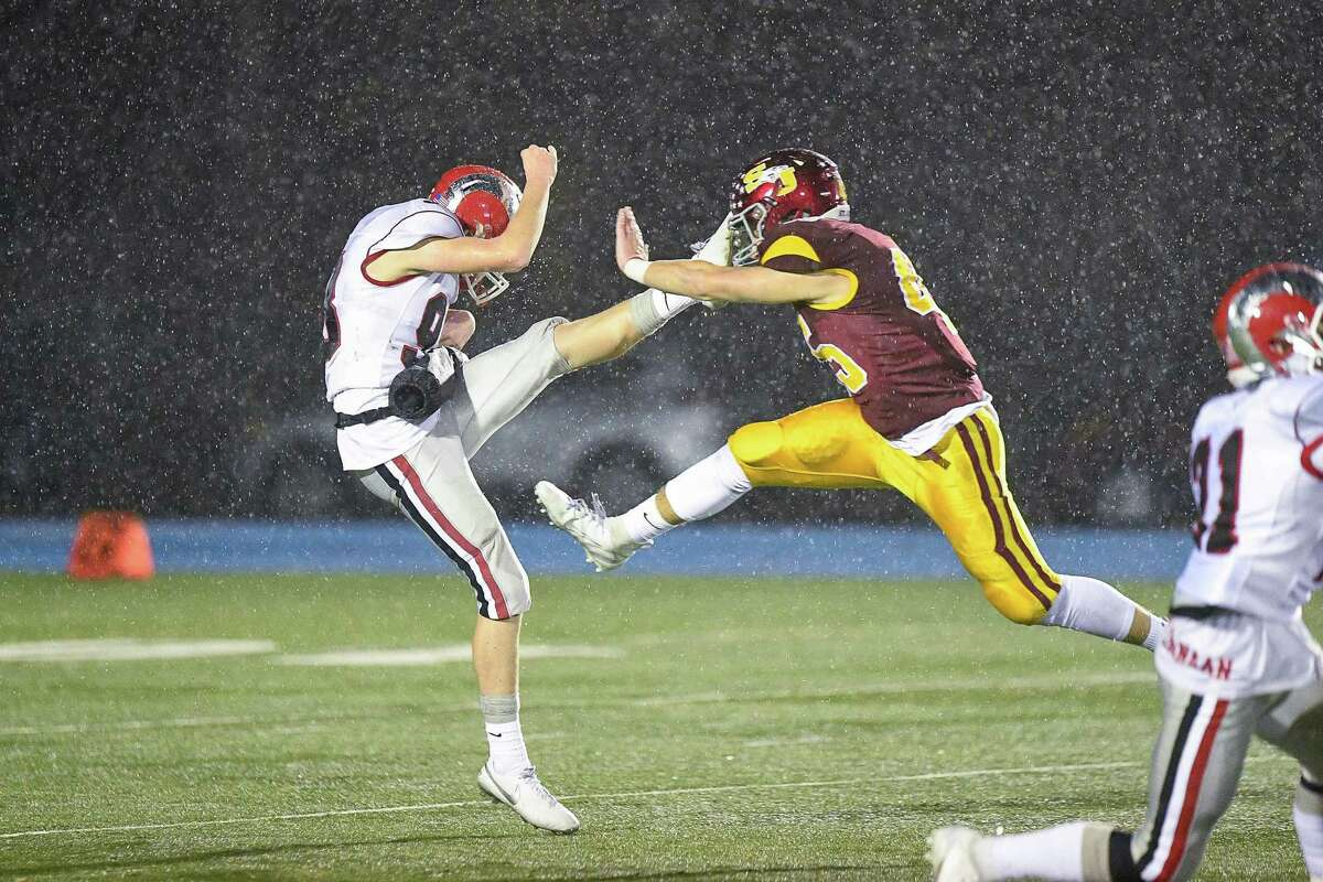 St. Joseph high's Dennis Rotunno blocks the punt by New Canaan's Nicholas Radman in the CIAC Class L Semi-final game at Bunnell High School, Monday December 9, 2019
