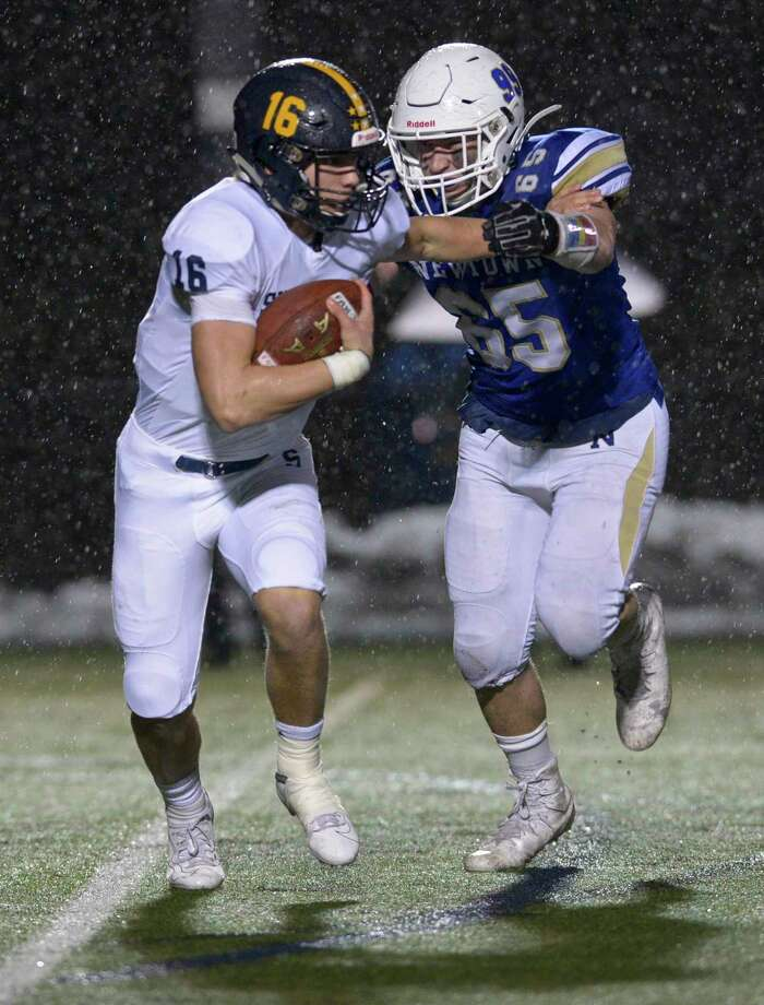 Newtown's James Knox (65) catches Simsbury quarterback Aiden Boeshans (16) in the backfield during the first half of the Class LL State Football semifinal game between No 4 Simsbury and No. 1 Newtown high schools, Monday December 9, 2019, at Newtown High School, Newtown, Conn. Photo: H John Voorhees III / Hearst Connecticut Media / The News-Times