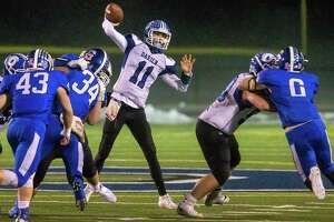 Darien quarterback Peter Graham gets off a pass under pressure from Southington's defense in their Class LL semifinal game Monday night in Southington. Darien won 21-12 to advance to the final.