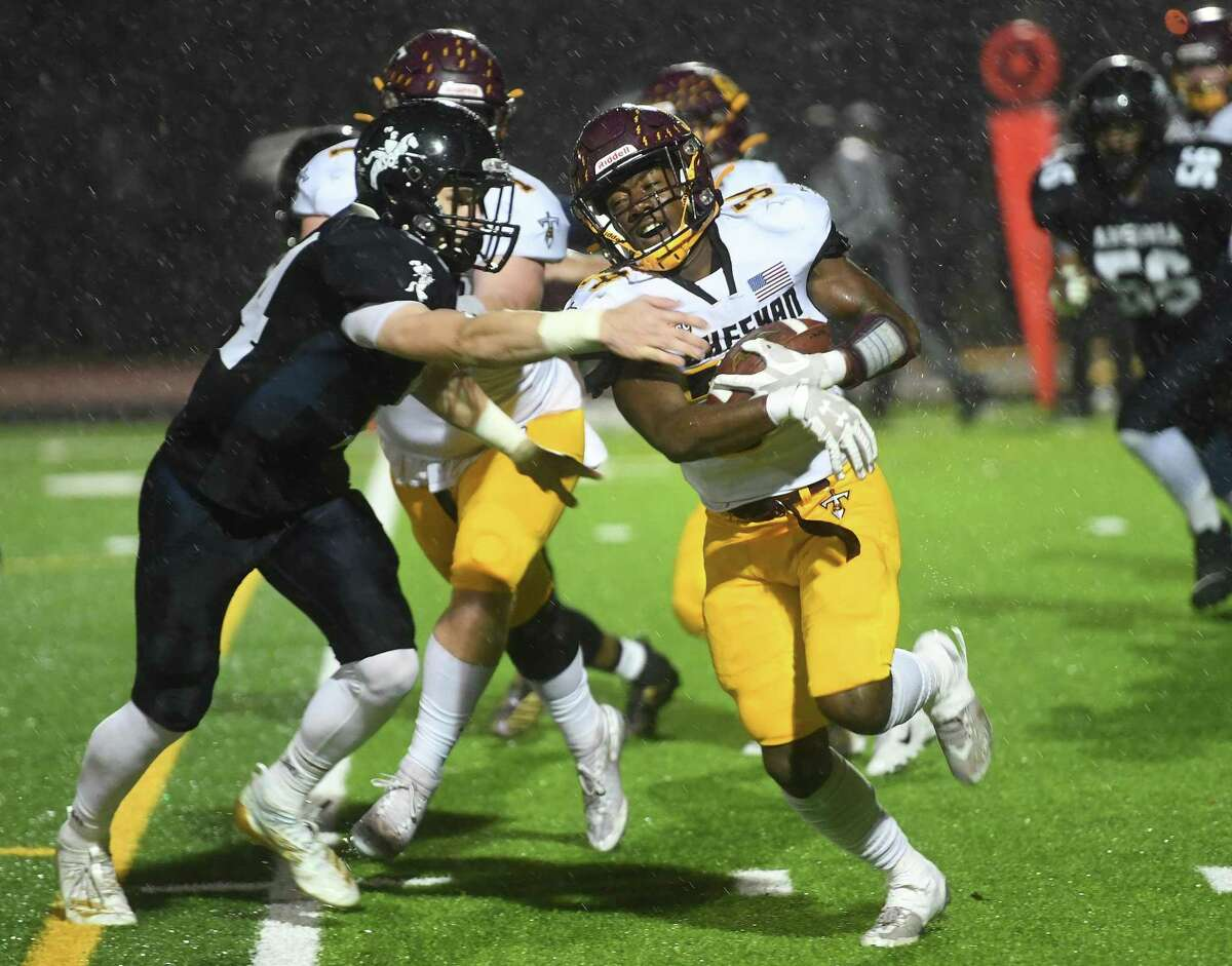 Ansonia's Noah Wagnblas looks to wrap up Sheehan runner Terrance Bogan in the first half of their Class S State Football semifinal at Ryan Field in Derby on Monday.