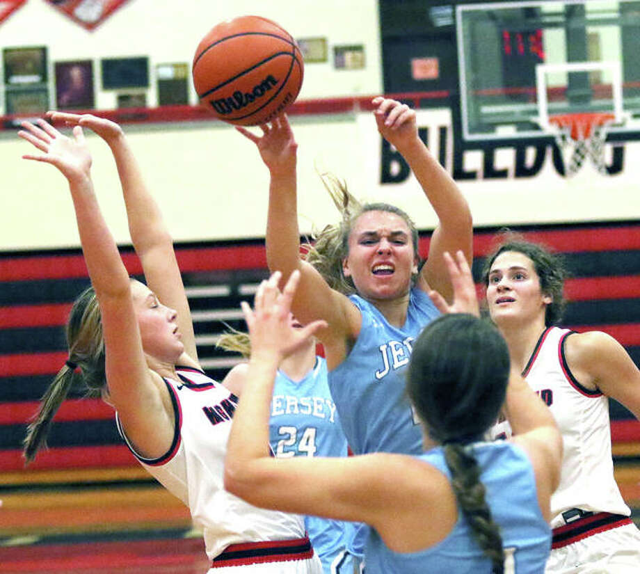 Jersey's Clare Breden (middle) delivers a pass out of traffic in the lane to teammate Bella Metzler under the basket Monday night at Highland. Photo: Greg Shashack | The Telegraph