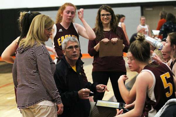 Deckerville girls basketball coach Doug Kirkpatrick talks strategy with his team during a timeout. The Eagles ran past North Huron on Monday night, 71-22.