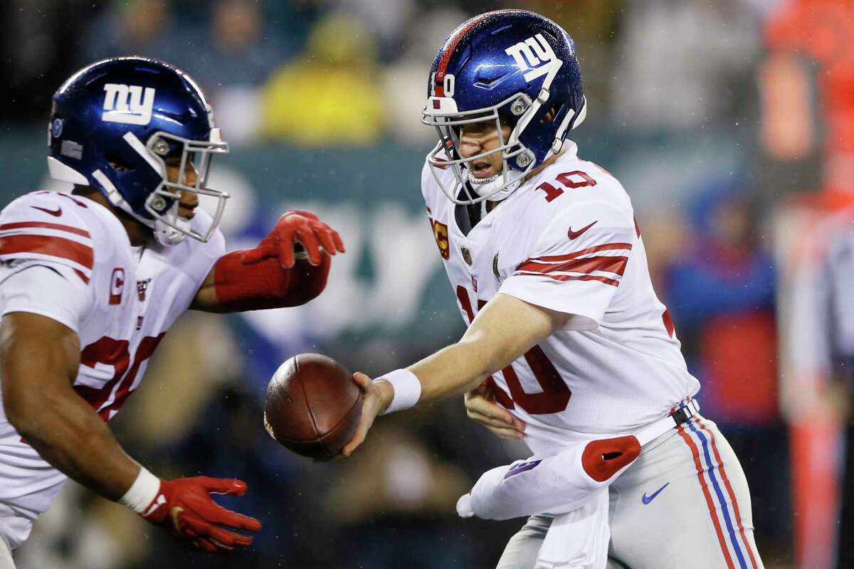 New York Giants' Eli Manning, right, hands off to Saquon Barkley during the first half of an NFL football game against the Philadelphia Eagles, Monday, Dec. 9, 2019, in Philadelphia. (AP Photo/Michael Perez)