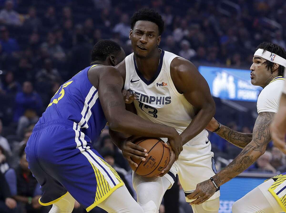 Memphis Grizzlies' Jaren Jackson Jr., center, keeps the ball from Golden State Warriors' Draymond Green during the first half of an NBA basketball game Monday, Dec. 9, 2019, in San Francisco. (AP Photo/Ben Margot)