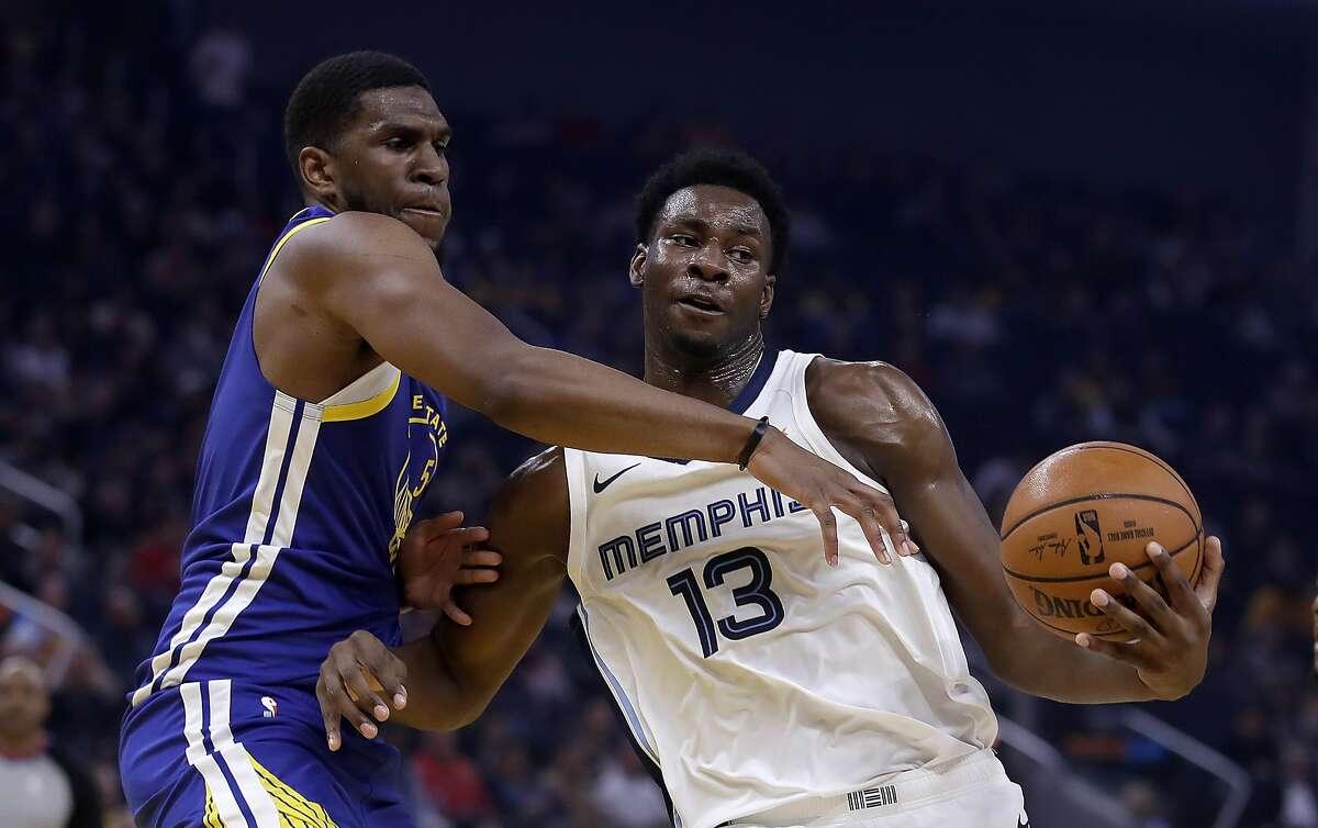 Memphis Grizzlies' Jaren Jackson Jr. (13) keeps the ball from Golden State Warriors' Kevon Looney, left, during the first half of an NBA basketball game Monday, Dec. 9, 2019, in San Francisco. (AP Photo/Ben Margot)