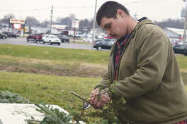 Bret Gann of Anderson's tree lot on West Morton Avenue trims an evergreen branch Monday before using it to make a wreath.