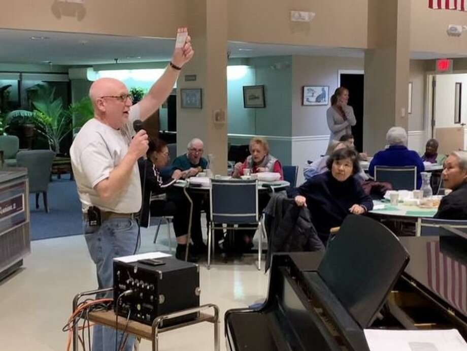 Wilton Volunteer Ambulance Corps president John Miscioscia calls out a raffle winner at a dinner presented by the corps at Ogden House. Photo: Contributed Photo / Wilton Volunteer Ambulance Corps / Wilton Bulletin