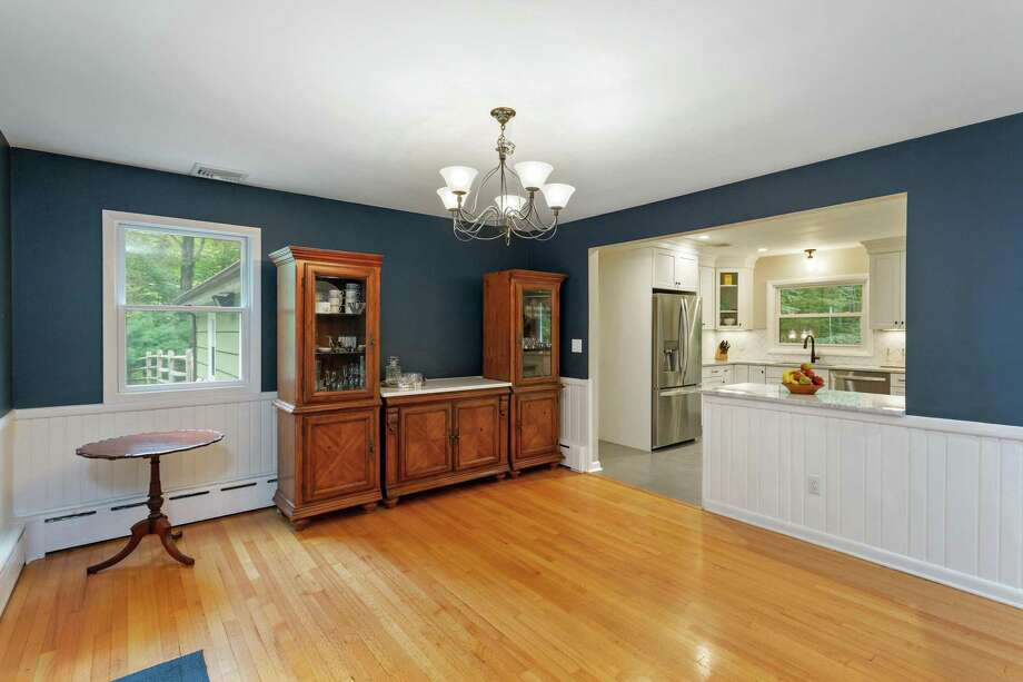 In the formal dining room there is paneling on the lower walls, sliding doors to the deck and backyard, and a serving counter.