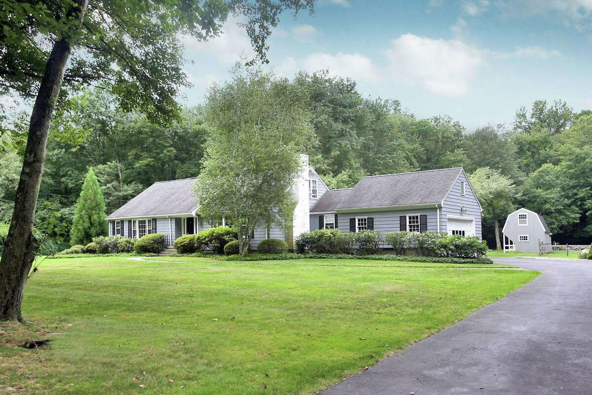 The light gray Cape Cod colonial house at 1163 Merwins Lane sits on a property of just over two acres in Greenfield Hills.