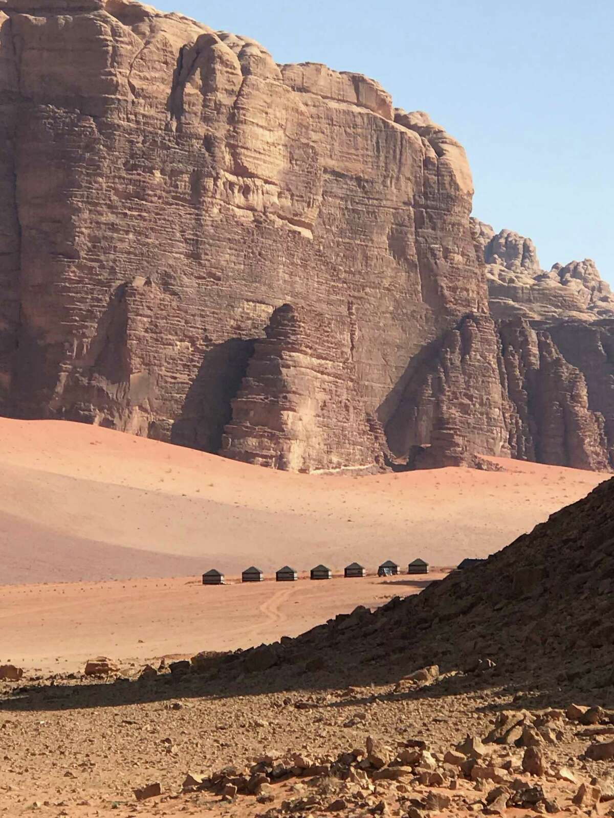 Bedouin camping tents are set up at the base of cliffs in the Wadi Rum desert, where many movies have been filmed.