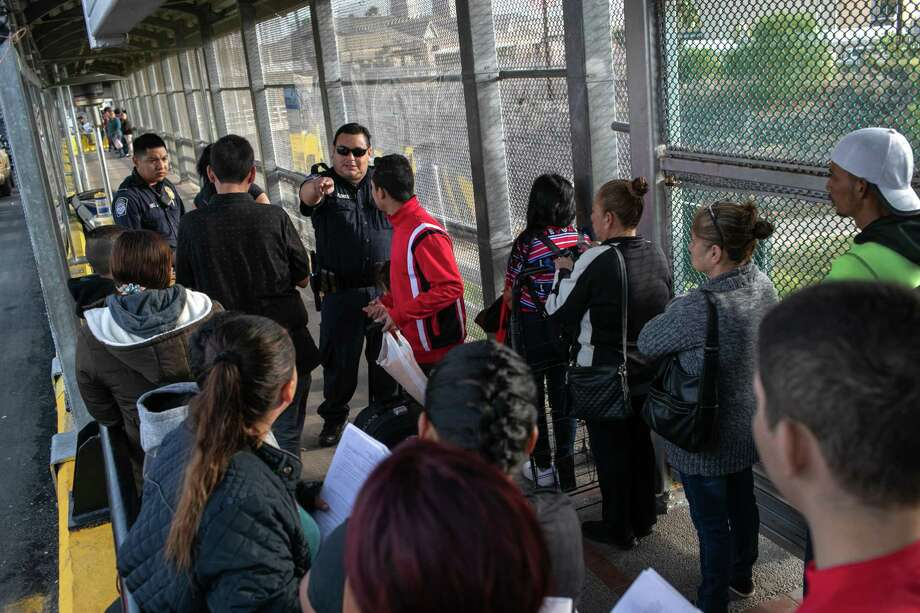 U.S. Customs and Border Protection officers instruct immigrant families to wait in line on the international bridge from Mexico to the United States next to the border town of Matamoros, Mexico. Photo: Getty Images / 2019 Getty Images