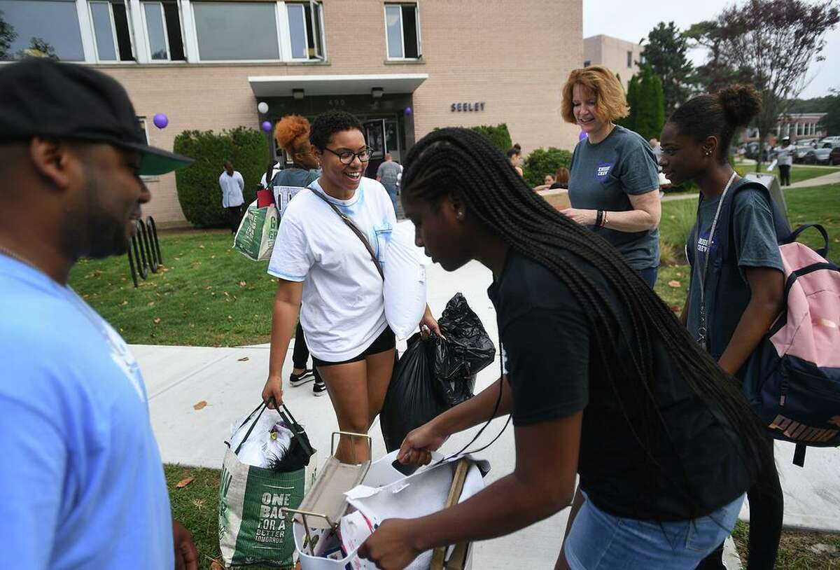 Incoming freshman Ayziah Abner, second from left, of Stratford, has lots of help moving in to the dorms including University President Laura Trombley, second from right, during move in day at the University of Bridgeport in Bridgeport, Conn. on Wednesday, August 21, 2019.