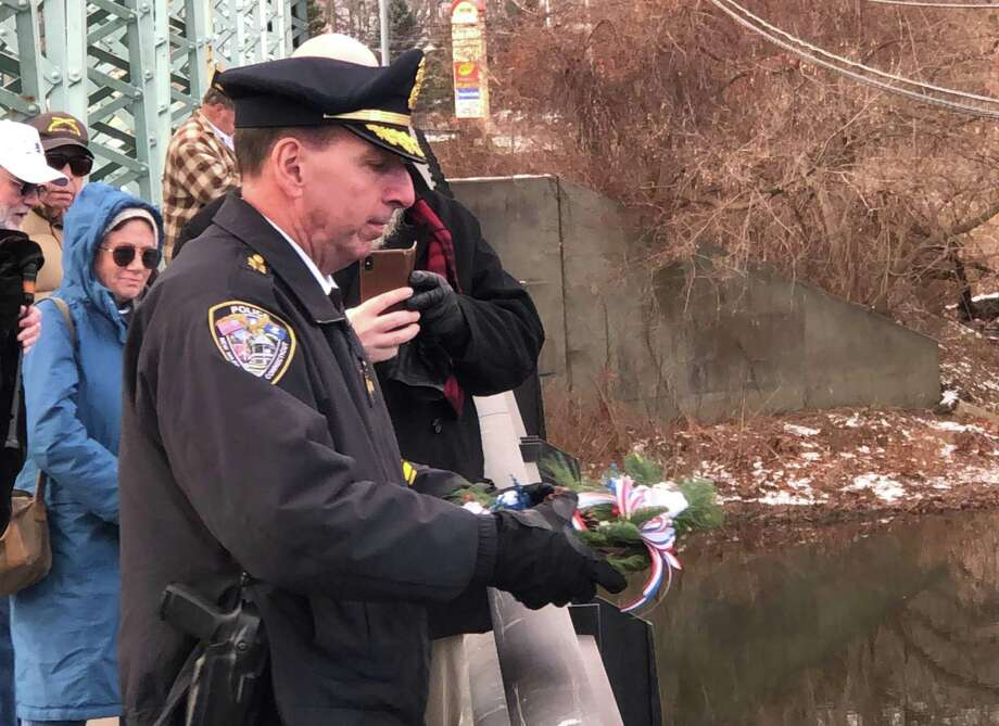 The New Milford Veterans Committee held its annual Pearl Harbor Remembrance Day ceremony Dec. 7. The ceremony, attended by veterans, residents and dignitaries, was held at the VFW Hall on Avery Road and was followed by a brief wreath ceremony at Veterans Memorial Bridge. Above, New Milford Police Chief Spencer Cerruto tosses the wreath into the Housatonic River in memory of those who lost their life at Pearl Harbor. Photo: Courtesy Of Jim Delancy / The News-Times Contributed
