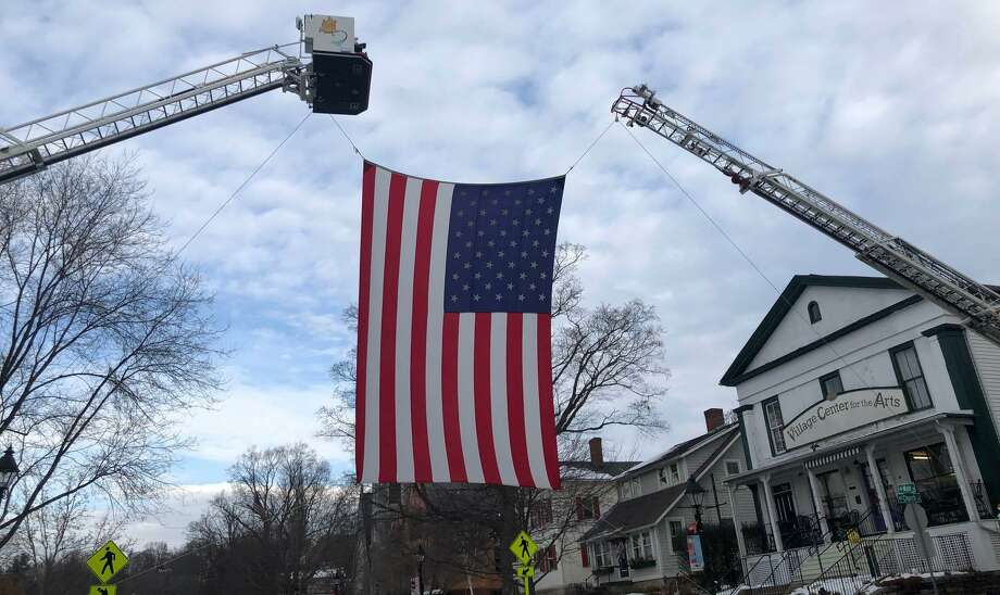 A large American flag draped across the north side of Main Street in New Milford last Friday paid tribute to Ronald J. Adams of New Milford. Adams, 71, died Nov. 29. Photo: Deborah Rose / Hearst Connecticut Media / The News-Times  / Spectrum