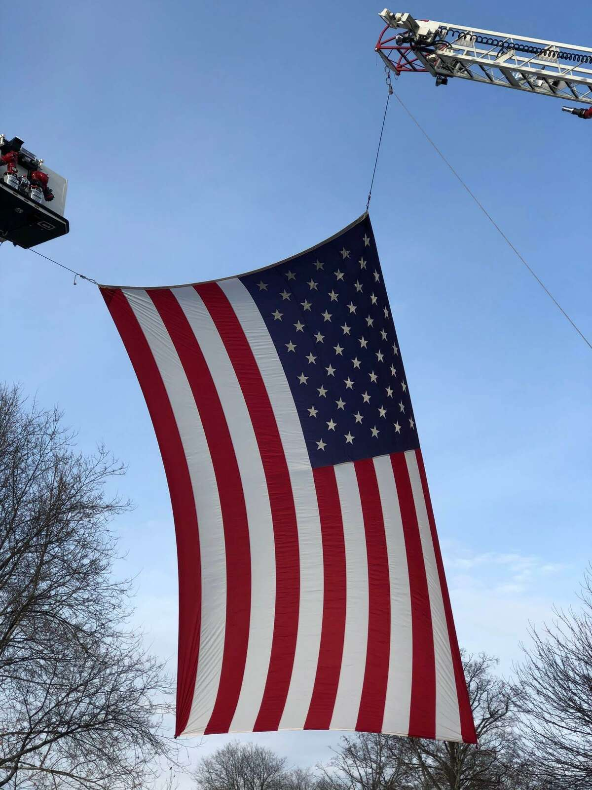 Spectrum/ A large American flag draped across the north side of Main Street in New Milford last Friday, Dec. 6, 2019, paid tribute to Ronald J. Adams of New Milford. Adams, 71, died Nov. 29 at his home. Firefighters from Water Witch Hose Co. #2 in New Milford and Newtown fire department hung the flag between New Milford's Tower 25 and Newtown's Truck 14 from the crossover near the bandstand to Church Street. A member of Iron Works Local #40, Adams had been of the construction of the World Trade Center. After 9/11, Adams stepped up and was part of the rescue/recovery efforts, which contributed to his disease.