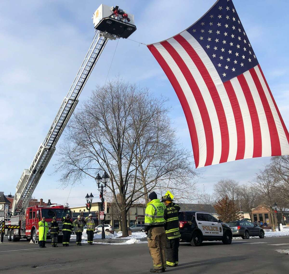 Spectrum/ A large American flag draped across the north side of Main Street in New Milford last Friday, Dec. 6, 2019, paid tribute to Ronald J. Adams of New Milford. Adams, 71, died Nov. 29 at his home. Firefighters from Water Witch Hose Co. #2 in New Milford and Newtown fire department hung the flag between New Milford's Tower 25 and Newtown's Truck 14 from the crossover near the bandstand to Church Street. A member of Iron Works Local #40, Adams had been of the construction of the World Trade Center. After 9/11, Adams stepped up and was part of the rescue/recovery efforts, which contributed to his disease. Above, Water Witch members, from left to right, on left, Bob Golembeski, Al Tani, David Golembeski, Lt. Sean Delaney and Chief Jim Ferlow, as vehicles in the procession make their way beneath the flag. New Milford Tower 25 and Newtown Truck 14