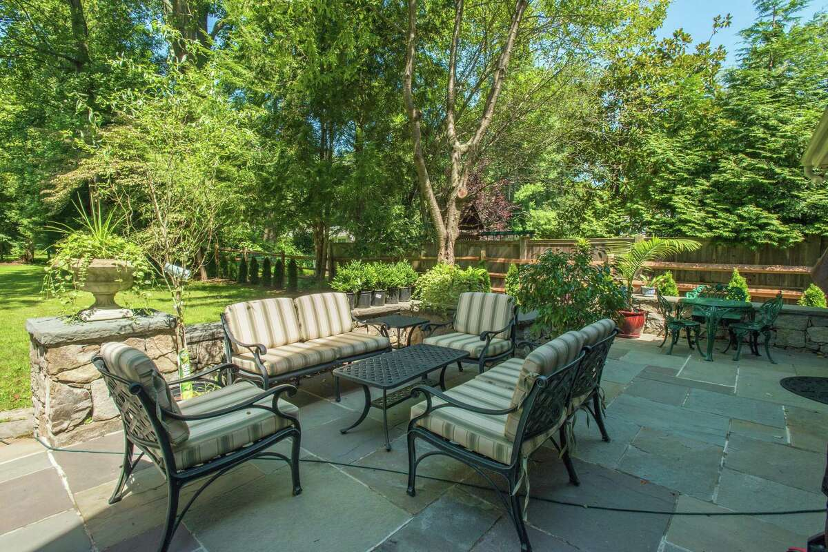 In the backyard there is a large flagstone patio with a stone sitting wall.