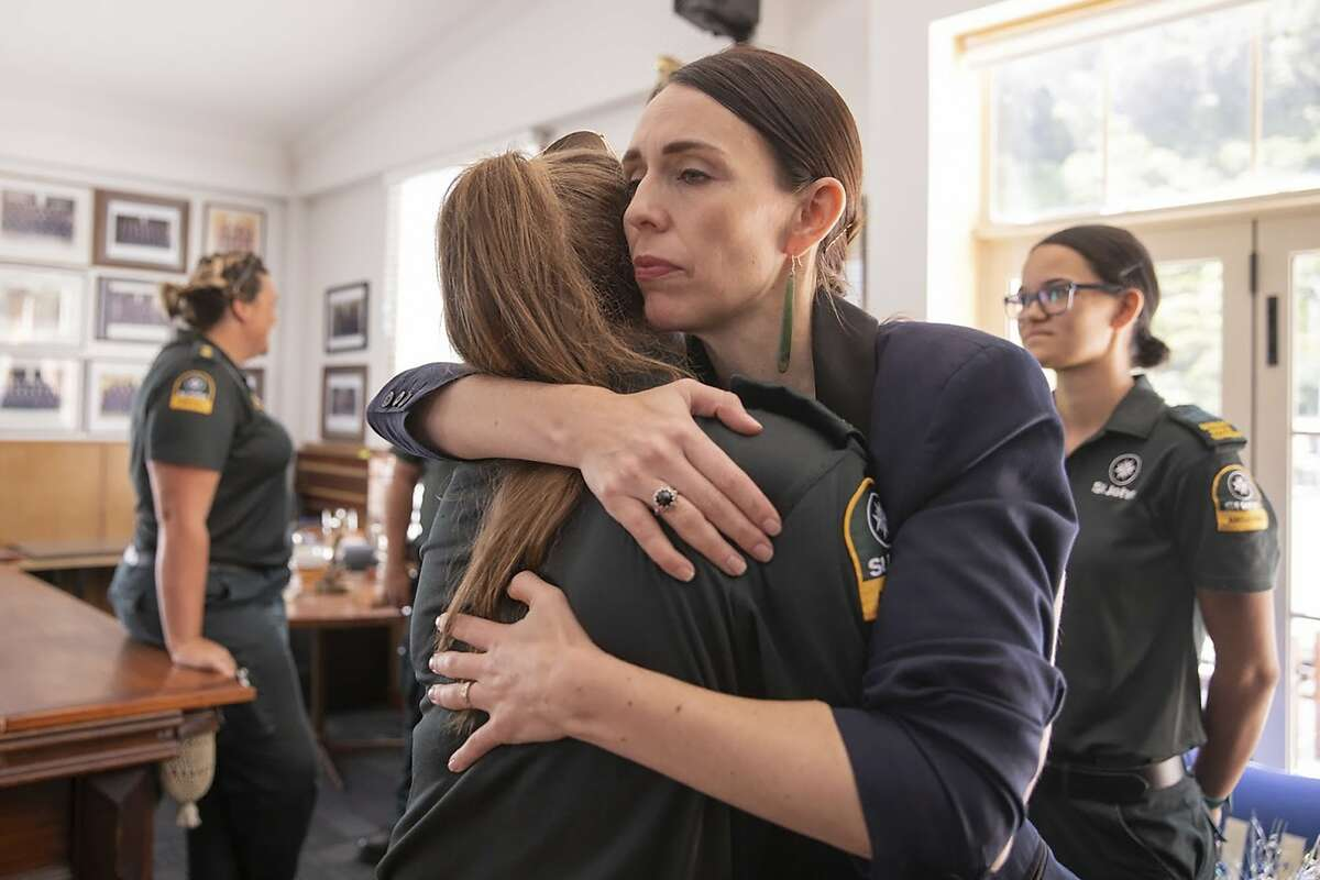 New Zealand's Prime Minister Jacinda Ardern, right, hugs a first responder in Whakatane, New Zealand, Tuesday, Dec. 10, 2019. A volcanic island in New Zealand erupted Monday Dec. 9 in a tower of ash and steam while dozens of tourists were exploring the moon-like surface, killing multiple people and leaving many more missing.(
