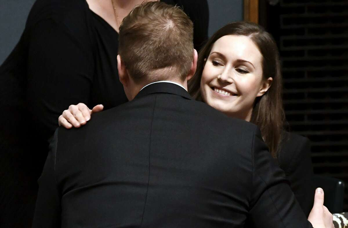 Social democrats minister Sanna Marin, right, is congratulated after she was elected as the new Prime Minister of Finland, in the session of the Finnish Parliament in Helsinki, Finland, on Tuesday, Dec. 10, 2019. Finland's parliament chose Sanna Marin as the country's new prime minister Tuesday, making the 34-year-old the world's youngest sitting head of government.