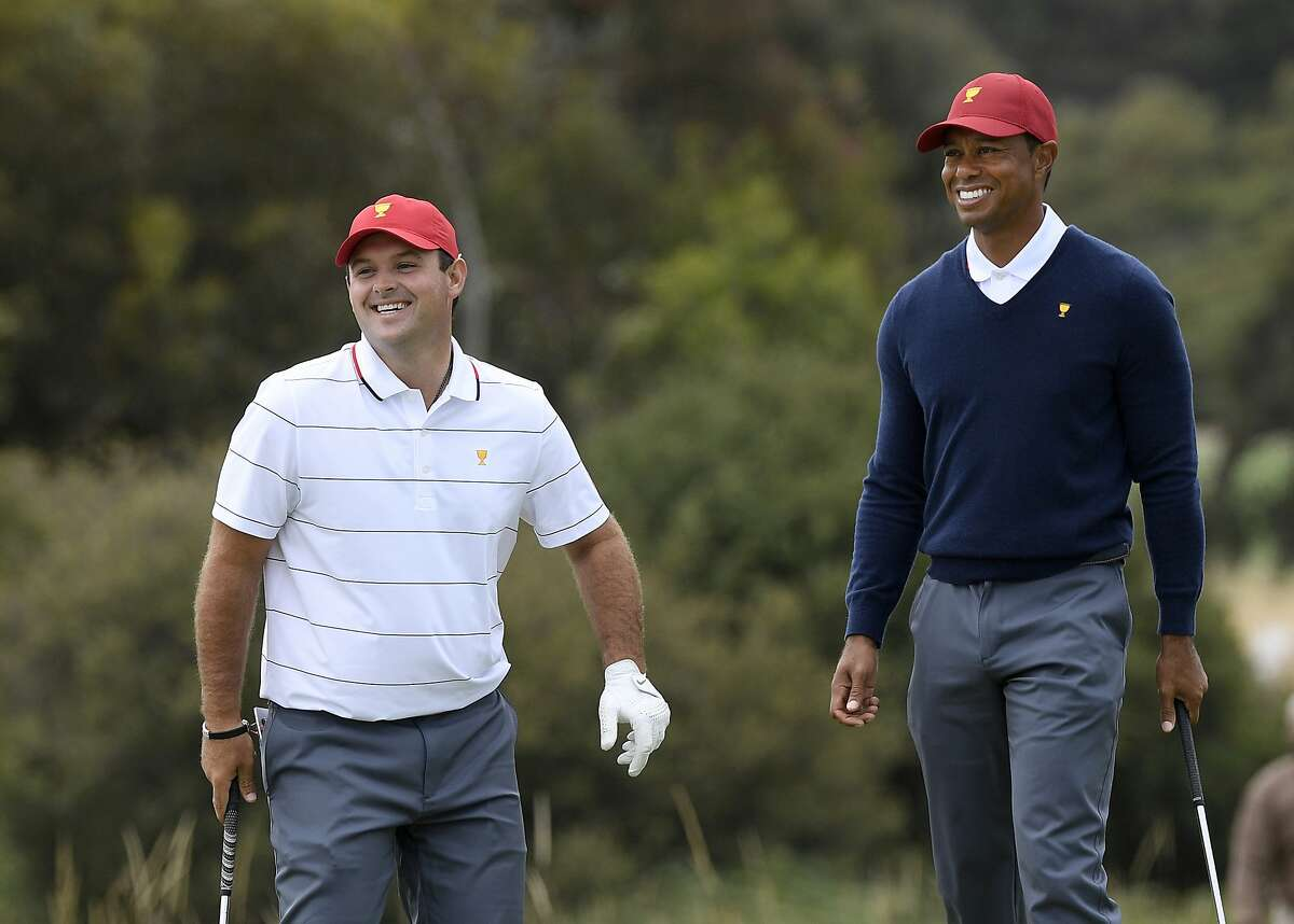 USA team's Patrick Reed, left, and captain Tiger Woods smile during a practice session ahead of the President's Cup Golf tournament in Melbourne, Tuesday, Dec. 10, 2019. (AP Photo/Andy Brownbill)