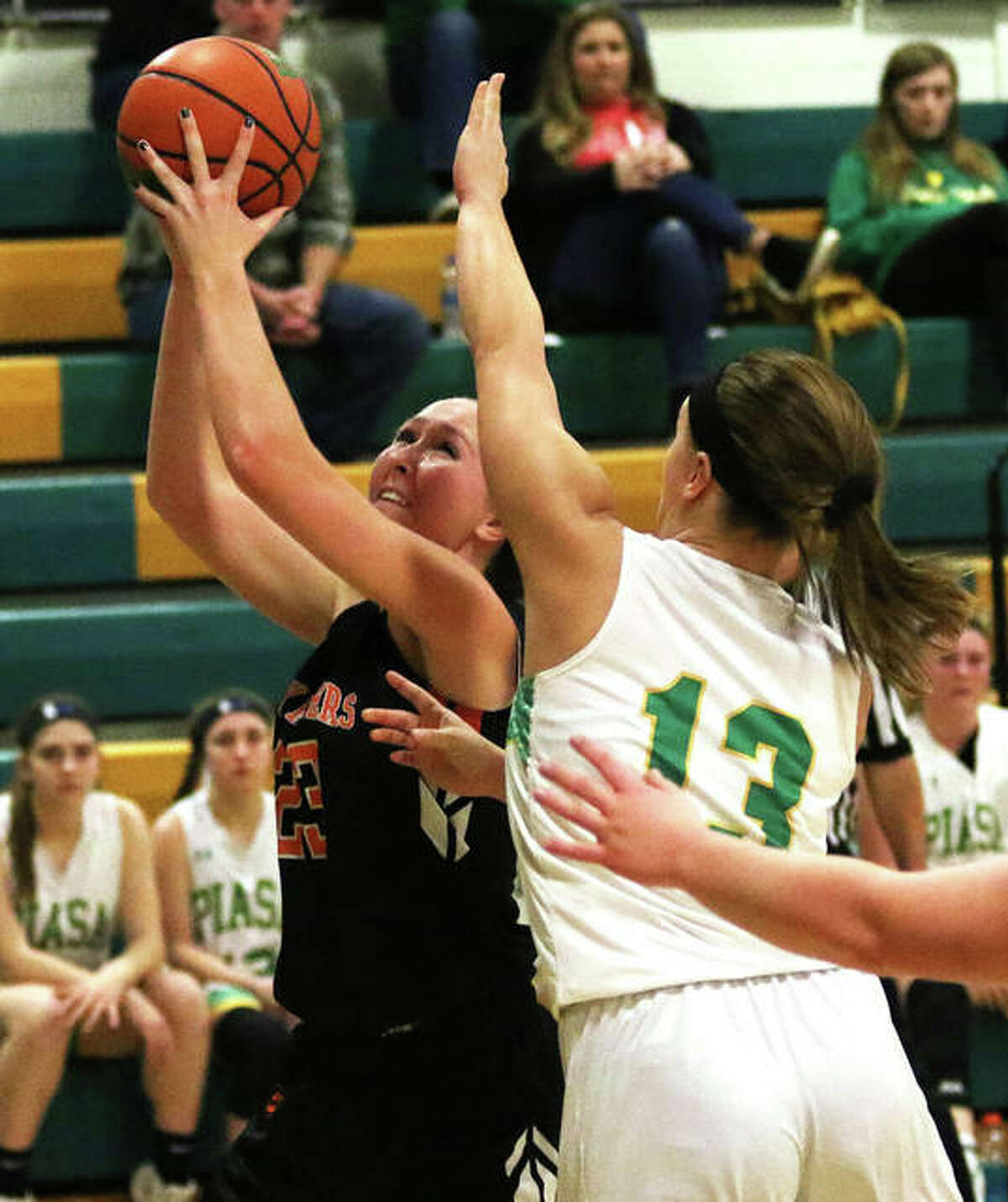 Gillespie's Emily Schmidt (left) goes up for a shot contested by Southwestern's Natalie Keith during a SCC girls basketball game Thursday in Piasa.