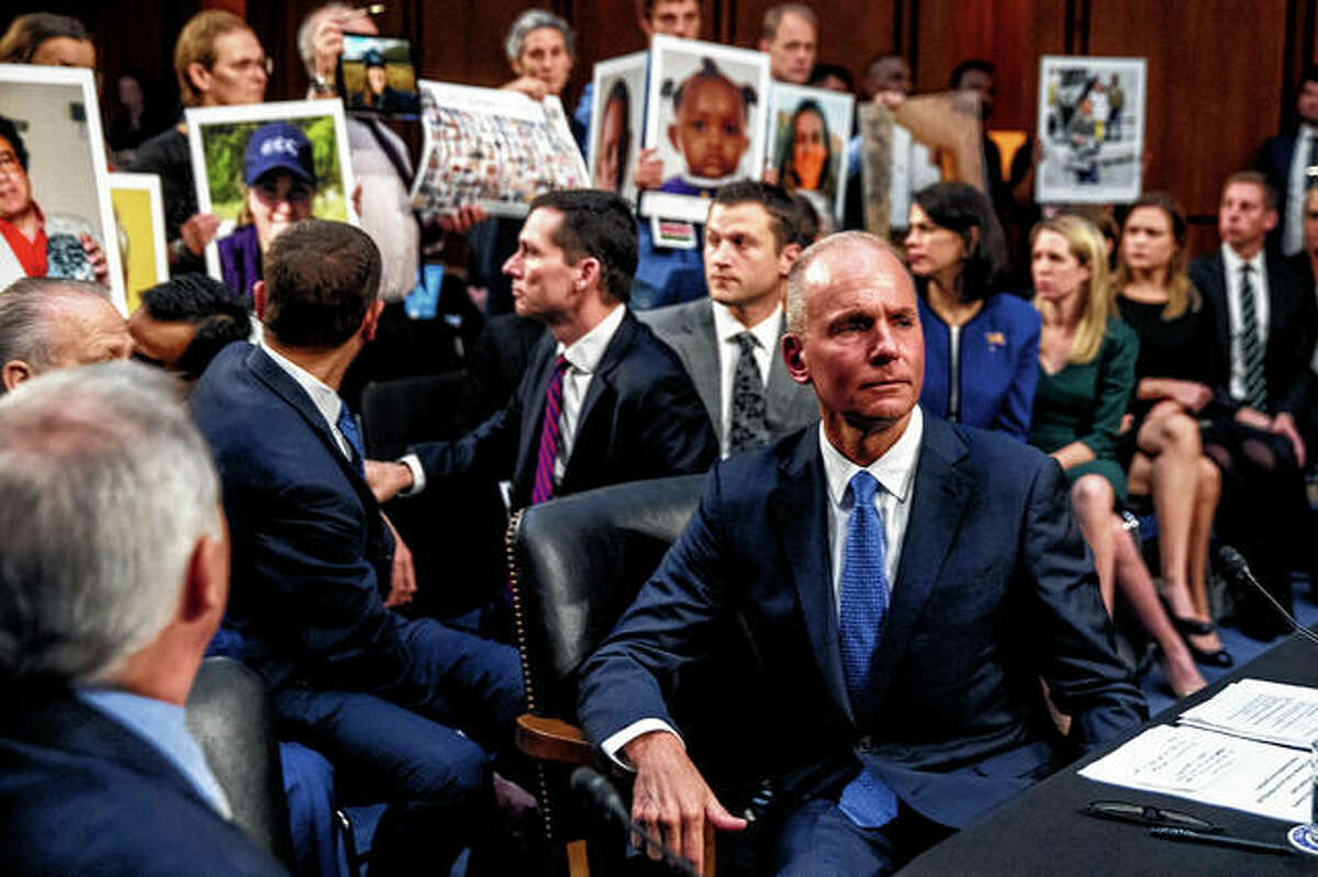 Boeing Company President and Chief Executive Officer Dennis Muilenburg (right foreground) watches Oct. 29 during a Senate Committee on Commerce, Science and Transportation hearing on Capitol Hillas as family members hold up photographs of those killed in the Ethiopian Airlines Flight 302 and Lion Air Flight 610 crashes.