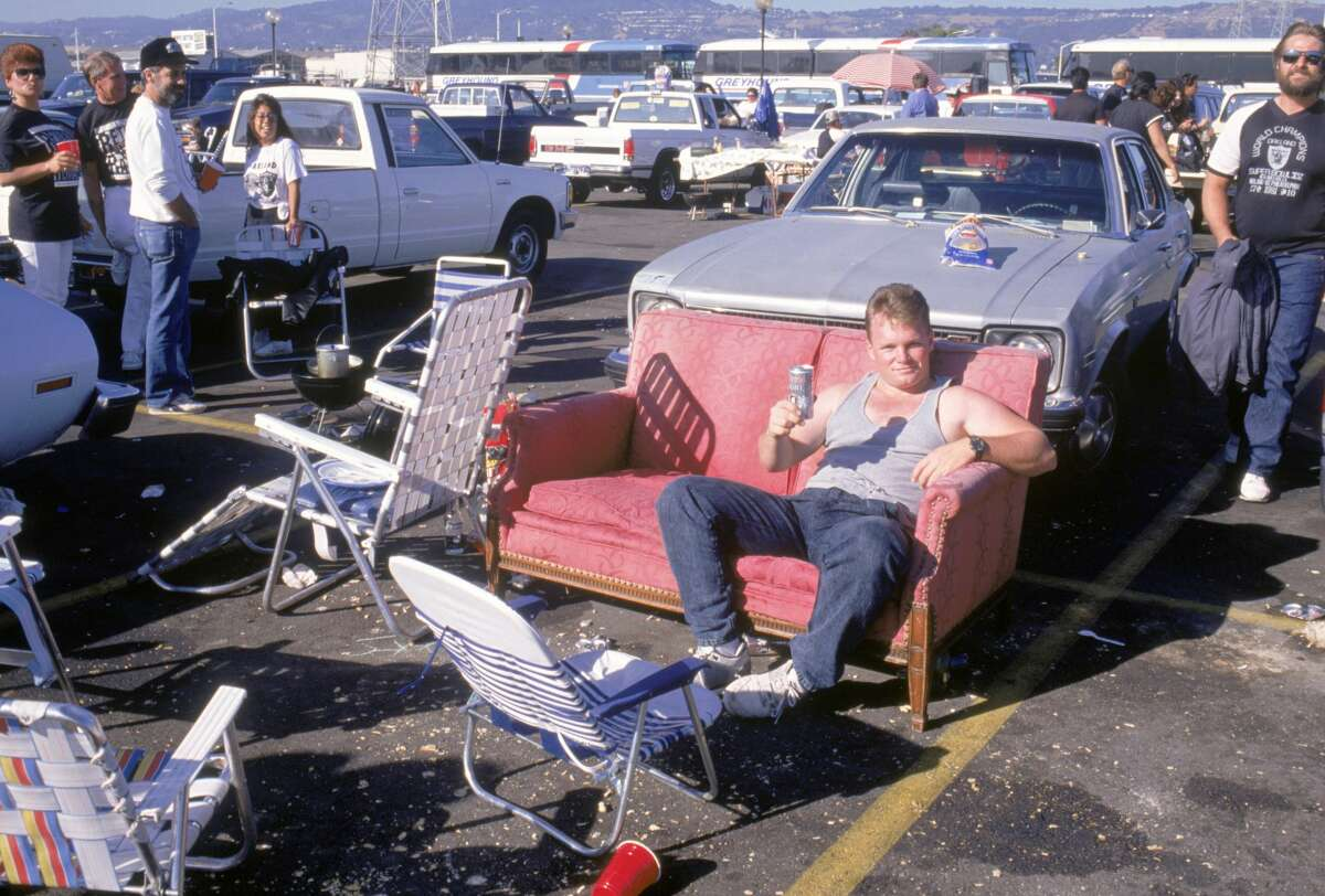 A fan holds a beer while posing for a portrait during a tailgate party prior to a preseason game at the Oakland/Alameda County Coliseum in Oakland, California.