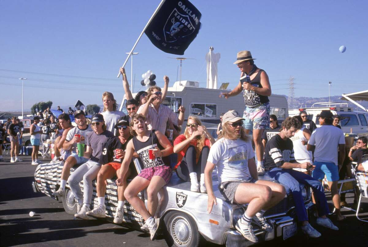 OAKLAND, CA - AUGUST 26: Fans wave a Raiders flag and sit on a silver car during a tailgate party before a preseason game against the Houston Oilers at the Oakland/Alameda County Coliseum in Oakland, California, on August 26, 1989. The Oilers won 23-21. The Los Angeles Raiders played this exhibition game in Oakland, attempting to generate interest in the team's possible return to Northern California. The Raiders moved back to Oakland in 1995. (Photo by George Rose/Getty Images)