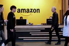 In this Nov. 13, 2018 file photo, employees walk through a lobby at Amazon's headquarters in Seattle. On Friday, May 3, 2019, shares in Amazon are moving higher after billionaire investor Warren Buffett said his firm has been buying the online retailer. (AP Photo/Elaine Thompson)
