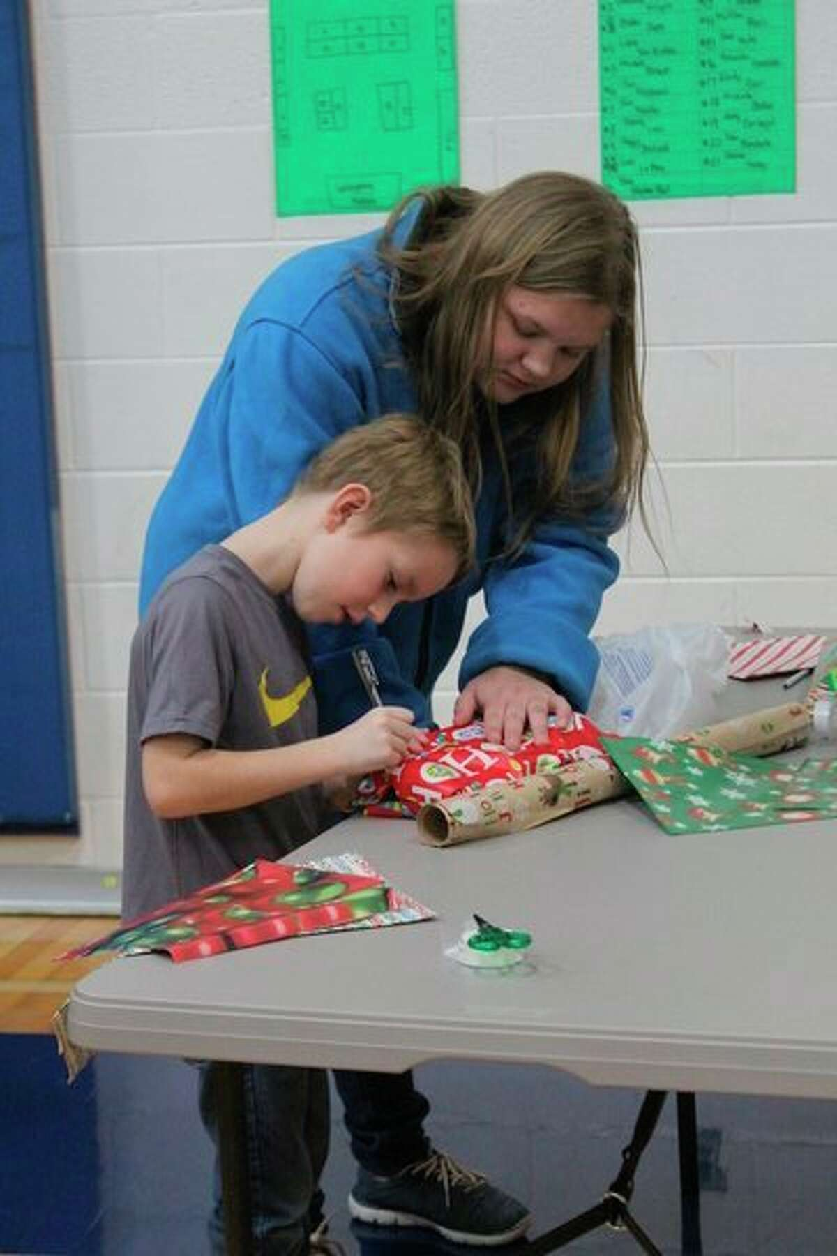 In one area of the gym, students gathered to get help writing their names on gift tags. (Pioneer photo/Catherine Sweeney)