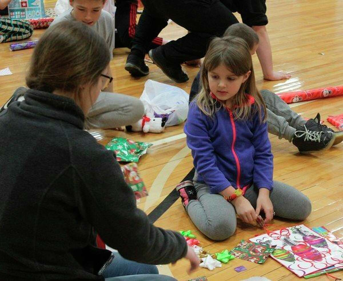 On one half of the gym, high school volunteers helped shoppers wrap their presents. High School students each spent an hour of their day volunteering at the holiday event. (Pioneer photo/Catherine Sweeney)