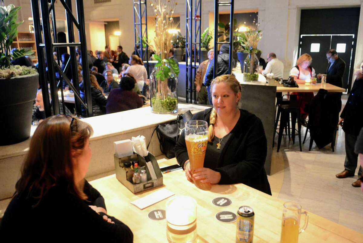 Jessica Materna, of Black Rock, enjoys a beer boot during the grand opening of Harlan Haus, a new beer hall and restaurant on State Street in downtown Bridgeport, Conn., on Tuesday Jan. 10, 2018.