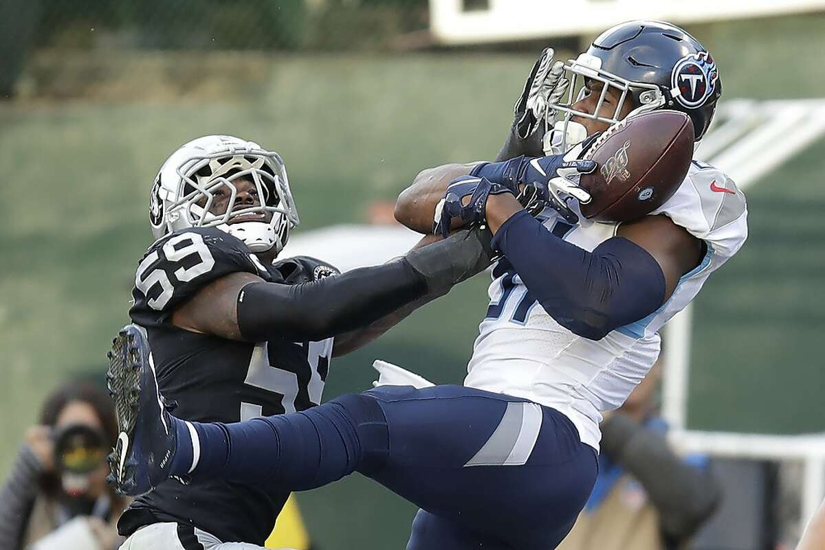 Tennessee Titans tight end Jonnu Smith, right, catches a touchdown pass against Oakland Raiders outside linebacker Tahir Whitehead (59) during the second half of an NFL football game in Oakland, Calif., Sunday, Dec. 8, 2019. (AP Photo/Ben Margot)