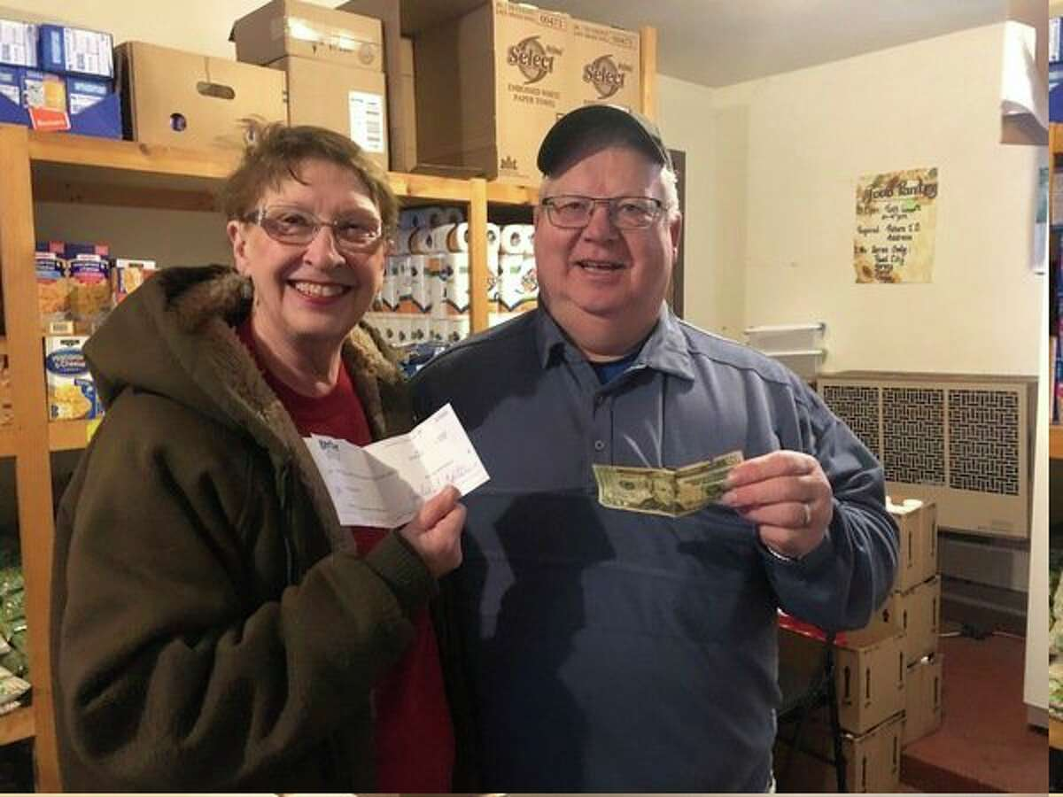 Nedra Ball and Humphrey VanderVlugt, who operate the Reed City Food Pantry, accept a check for $1,120 from Gerber Construction. Owners Bill and Jill Terryn matched $10 donations for every participant in the Trinity Lutheran Church and School Prepare For Pie 5k run and walk on Thanksgiving day. (Submitted photo)