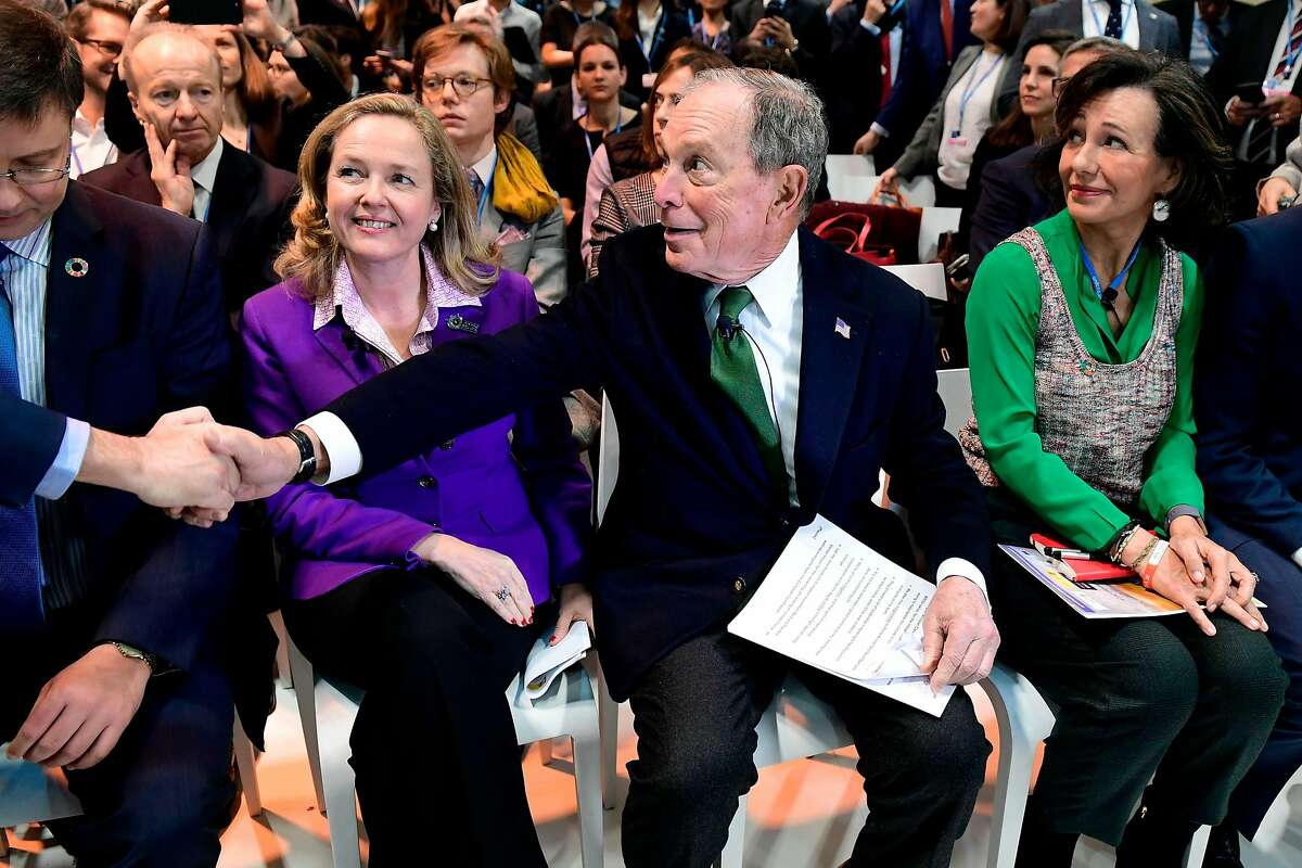 Democratic presidential hopeful Michael Bloomberg (C) sits between Spanish Santander Bank executive chairperson Ana Botin (R) and Spanish careteker minister for economic affairs Nadia Calvino as they attend an event within the UN Climate Change Conference COP25 at the 'IFEMA - Feria de Madrid' exhibition centre, in Madrid, on December 10, 2019. - UN climate negotiations in Madrid remained bogged down yesterday in the fine print of the Paris treaty rulebook, out-of-sync with a world demanding action to forestall the ravages of global warming. The 196-nation talks should kick into high-gear today with the arrival of ministers, but on the most crucial issue of all -- slashing the greenhouse gas emissions overheating the planet -- major emitters have made it clear they have nothing to say. (Photo by CRISTINA QUICLER / AFP) (Photo by CRISTINA QUICLER/AFP via Getty Images)