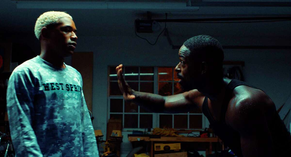 This image released by A24 shows Kelvin Harrison Jr., left, and Sterling K. Brown in a scene from