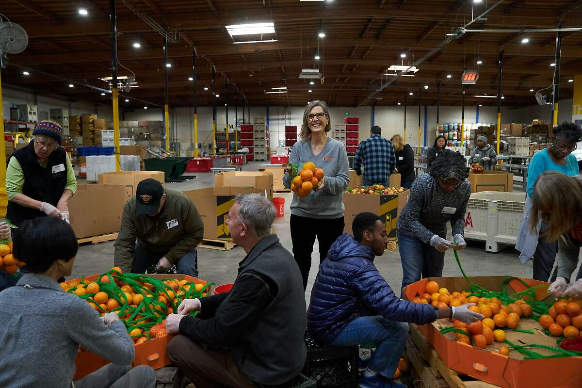 Suzan Bateson, Executive Director of the Alameda County Community Food Bank, holds oranges next to volunteers on Tuesday, Dec. 3, 2019, in Oakland, Calif.