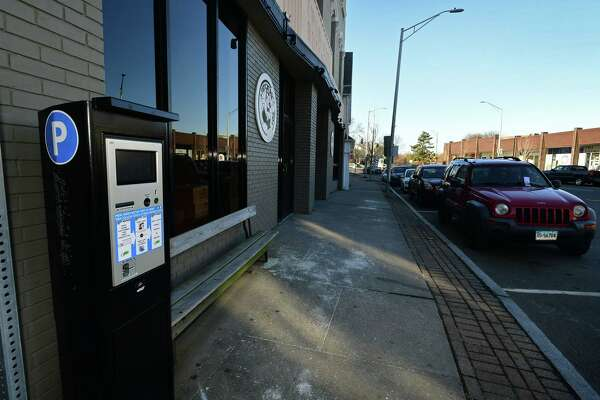 Parking kiosks in the Wall Street area Saturday, December 7, 2019, in Norwalk, Conn. The city has suspended enforcement in the area until they can find a better solution for metered parking that will satisfy area businesses in the distict. The city has covered signs and to clarify parking is temporarily free and lines have been painted on High Street to delineate street parking within the Wall Street master parking plan.