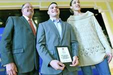 West Haven, Connecticut - Tuesday, December 10, 2019: Chris Liggio, center, a University of New Haven Football player, flanked by a David Whitehead, the Hartford HealthCare Executive Vice President and Chief Strategy and Transformation Office, left, and Rebecca Lobo, former University of Connecticut Basketball player and the Hartford HealthCare Courage Award Ambassador, poses for a photo after he was honored with the Hartford HealthCare Connecticut Courage Award Tuesday during a ceremony at the University of New Haven in West Haven. The Hartford HealthCare Connecticut Courage Award is presented every month to two inspiring Connecticut college student-athletes who have demonstrated courage in the face of adversity.