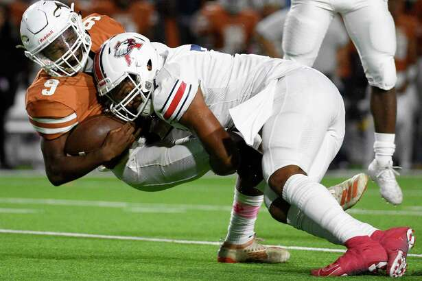 Dobie quarterback Cameron Gray, left, is sacked by Atascocita defensive lineman Asyrus Simon during the first half of a high school football game, Friday, Oct. 18, 2019, in Pasadena, TX.
