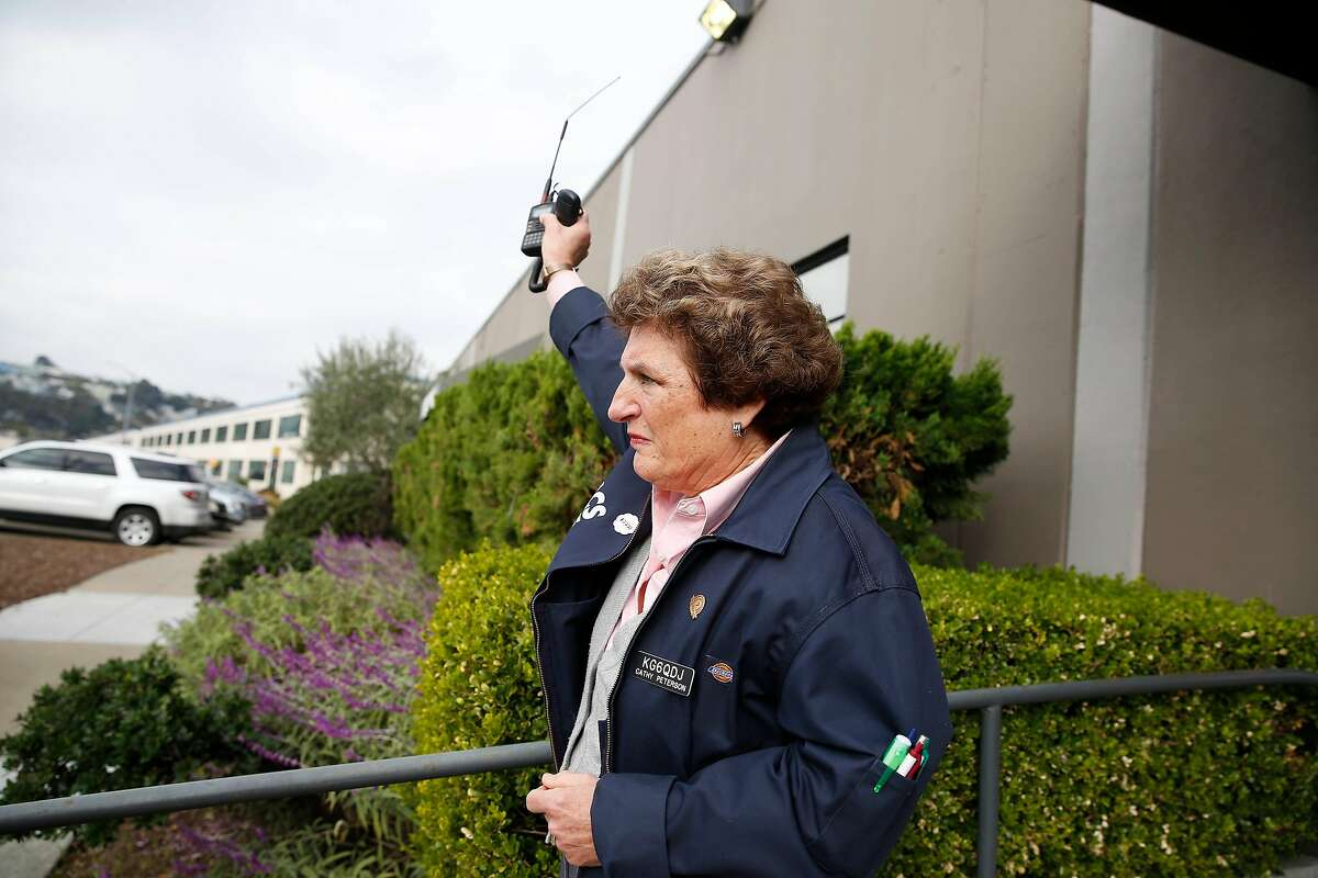Cathy Peterson, membership lead and volunteer Auxiliary Communications Service, holds her handy talkie in the air after noticing a delay while waiting to hear the noon warning sirens sound on Tuesday, December 10, 2019 in San Francisco, Calif. San Francisco warning sirens will do their last blaring on Tuesday December 10, 2019 before a two-year overhaul of the system.